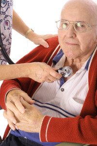nurse checking elderly mans heart